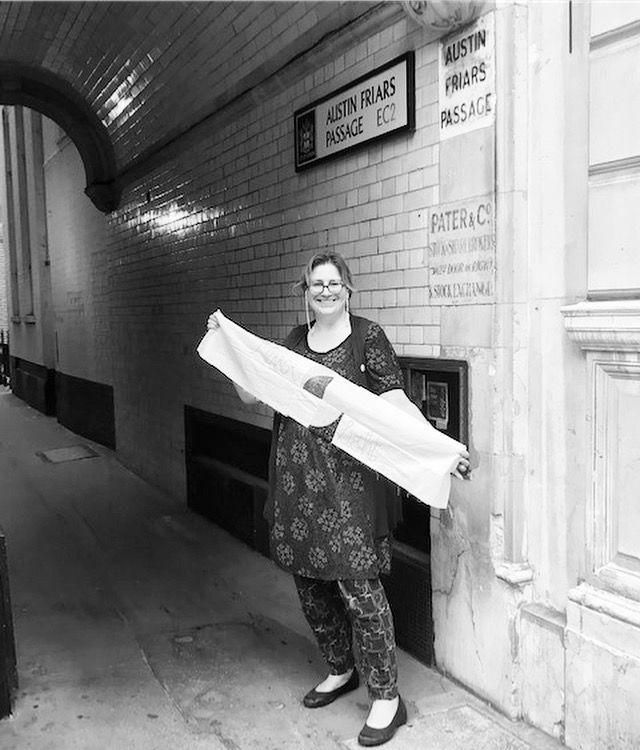 Author holding stitched fabric under a sign that reads Austin Friars Passage