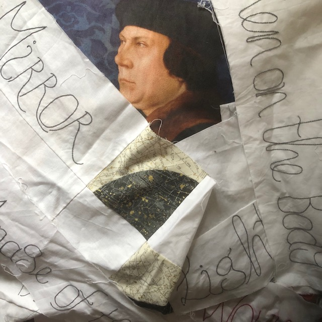 A cushion showing Thomas Cromwell with stitched wording in strips